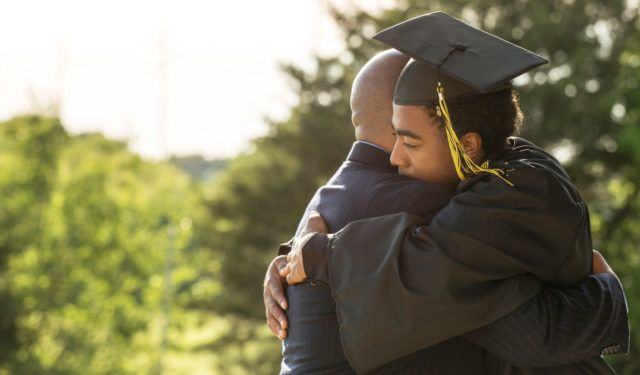 son hugs his father after graduating